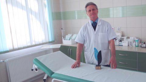 Lekarz stojący przy pustym łóźku na którym leży nagroda chirurga roku